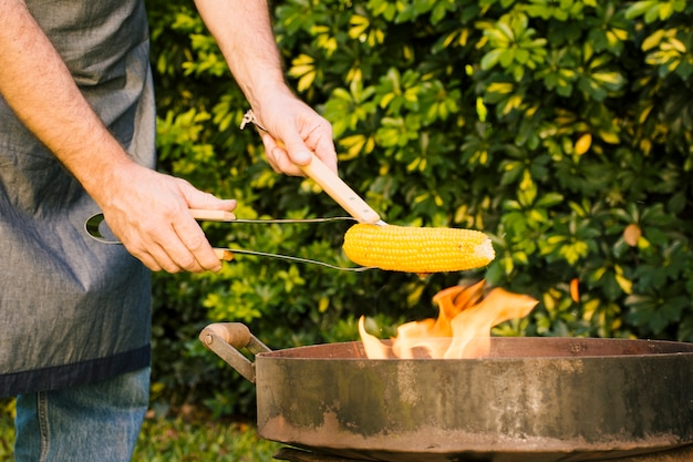 Milho amarelo saboroso em pinças de metal na grelha de fogo nas mãos