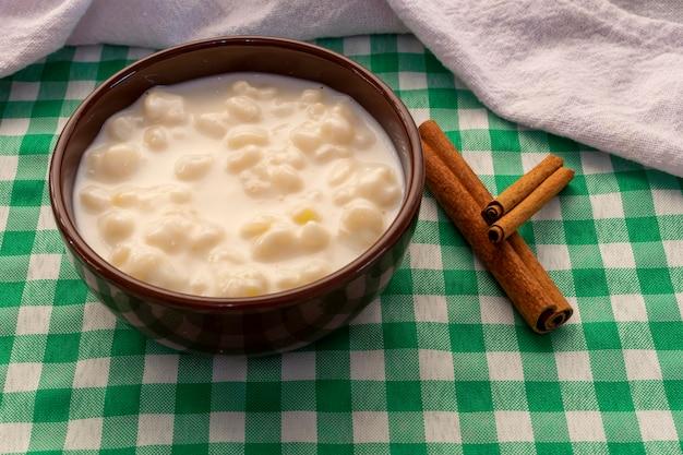 Milho branco cozido com leite conhecido como canjica, canjica ou mungunza, com canela em pau, em uma tigela sobre uma toalha verde.