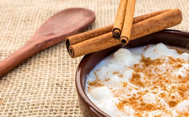 Milho branco cozido com leite conhecido como canjica, canjica ou mungunza, com canela, em uma tigela sobre uma mesa rústica.