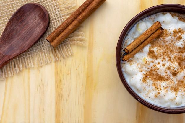 Milho branco cozido com leite conhecido como canjica, canjicão ou mungunza, com canela, em uma tigela rústica sobre uma mesa de madeira. vista do topo