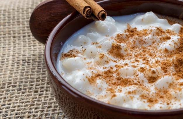 Milho branco cozido com leite conhecido como canjica ou mungunza, com canela, em uma tigela sobre uma mesa rústica.