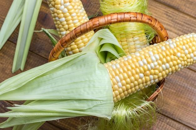 Milho cru com folhas na cesta de vime. fechar-se. fundo de madeira. postura plana