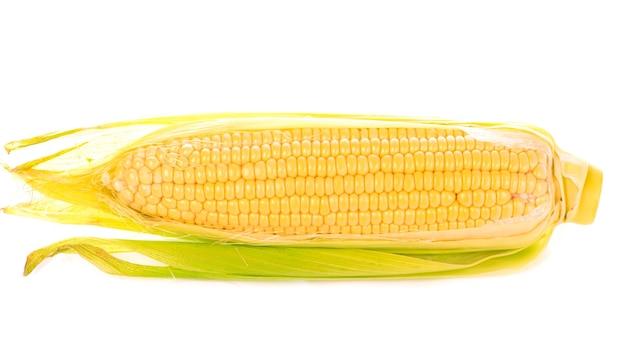 Milho cru com folhas verdes em uma superfície branca