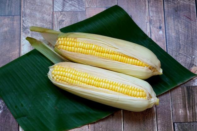 Milho doce orgânico em folha de bananeira e fundo de madeira