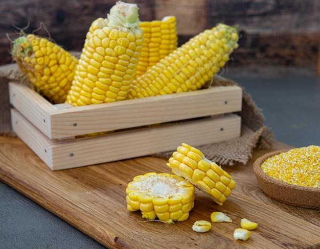 Milho doce orgânico, milho fresco recolhido em umas caixas de madeira. eleve a colheita, a produção do milho, a agricultura orgânica, a produção alimentar e o crescimento vegetal.