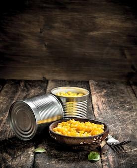 Milho em lata em uma lata com garfo na mesa de madeira.