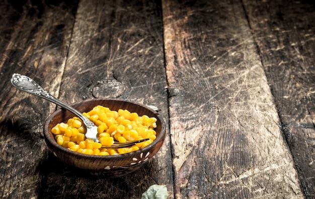 Milho enlatado em uma tigela na mesa de madeira.