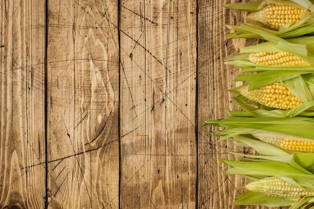 Milho fresco em espigas na tabela de madeira rústica, close up. espaço da cópia