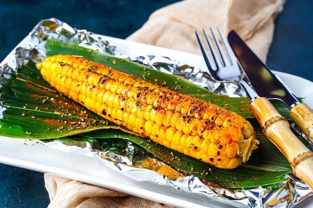 Milho fresco grelhado em um prato com pimenta e especiarias churrasco espiga de milho churrasco de refeição de vegetais vegan