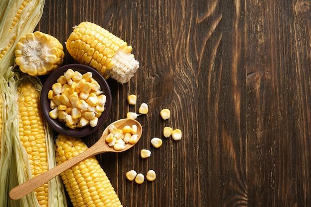 Milho fresco na espiga de milho em um fundo de madeira, lugar para texto, vista superior.