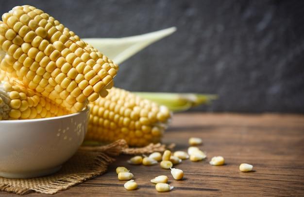 Milho fresco no saco e semente de milho doce na mesa de madeira rústica