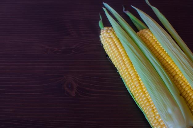Milho. orelhas de milho doce maduro em folhas e fundo de madeira
