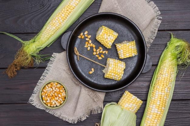 Milho picado na frigideira. duas espigas de milho na mesa. grãos de milho em uma tigela. fundo de madeira. postura plana