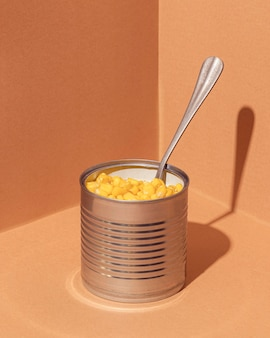 Milho preservado de alto ângulo em lata com garfo