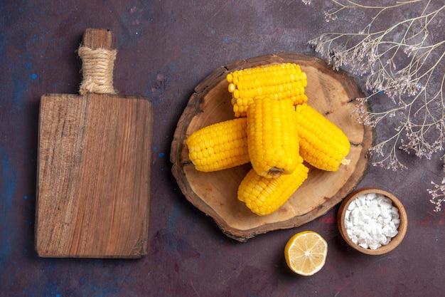 Milhos amarelos frescos com limão na superfície escura, alimentos de milho, lanche fresco cru