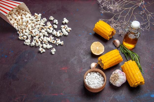 Milhos amarelos frescos com pipoca na mesa escura, vista de cima, salgadinhos de milho crus frescos