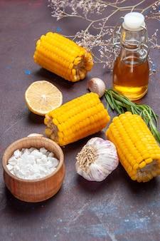 Milhos amarelos frescos de vista frontal com alho na superfície escura salgadinhos de milho crus frescos