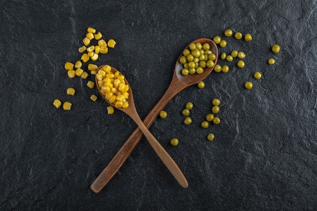 Milhos enlatados e ervilhas com colheres.