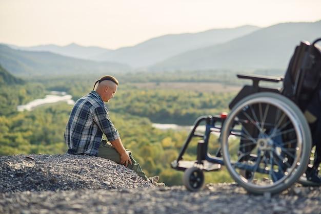 Militar com deficiência, sentado na montanha perto de cadeira de rodas, com as mãos levantadas e desfrutando do ar fresco