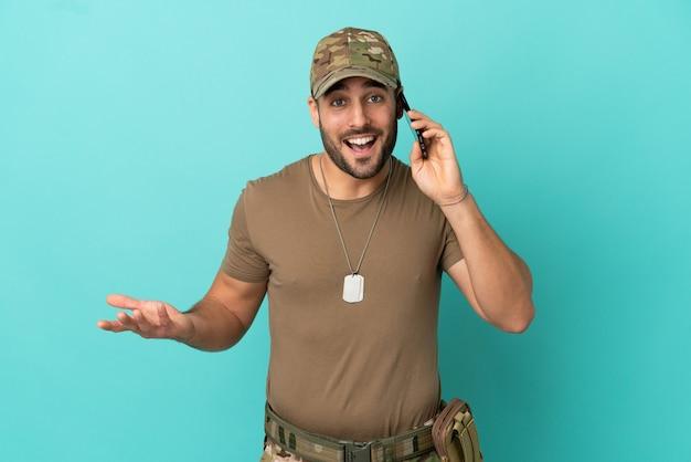 Militar com dog tag isolado em fundo azul, mantendo uma conversa com alguém no telefone celular