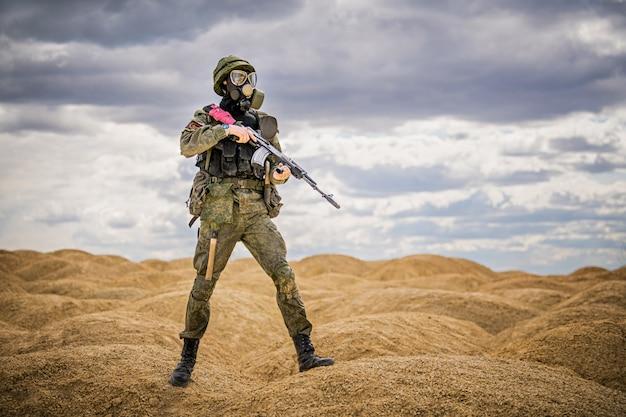Militar com máscara de gás e arma em pé no meio das colinas arenosas