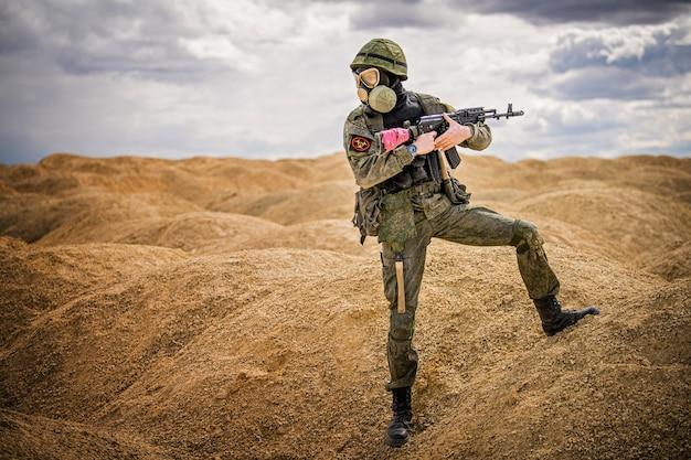 Militar com máscara de gás e arma em pé no meio do deserto