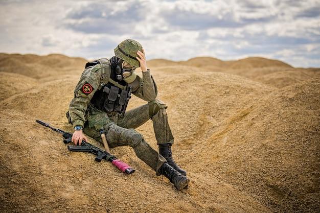 Militar com máscara de gás e arma sentado entristecido no meio do deserto