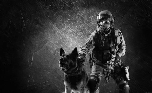 Militar de uniforme com uma arma nas mãos ataca o cão pastor contra um criminoso. mídia mista