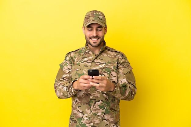 Militar isolado em fundo amarelo enviando mensagem com celular