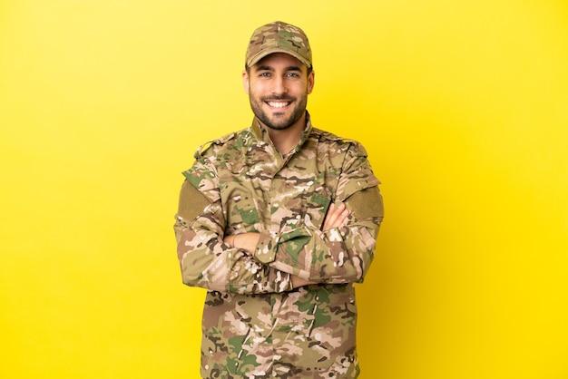 Militar isolado em fundo amarelo mantendo os braços cruzados na posição frontal