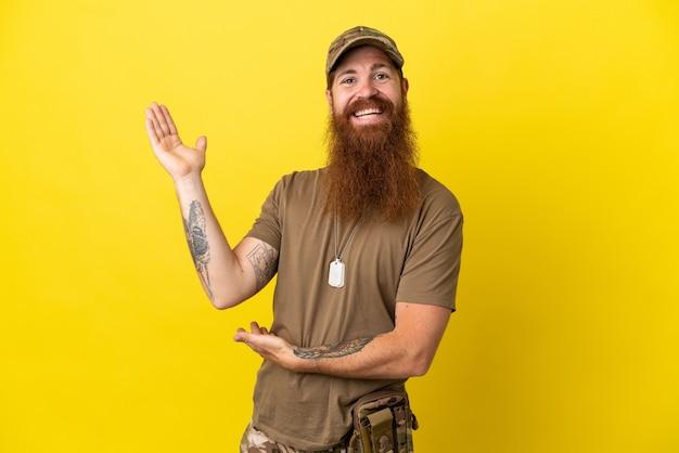 Militar ruivo com crachá isolado em fundo amarelo estendendo as mãos para o lado para convidar para vir