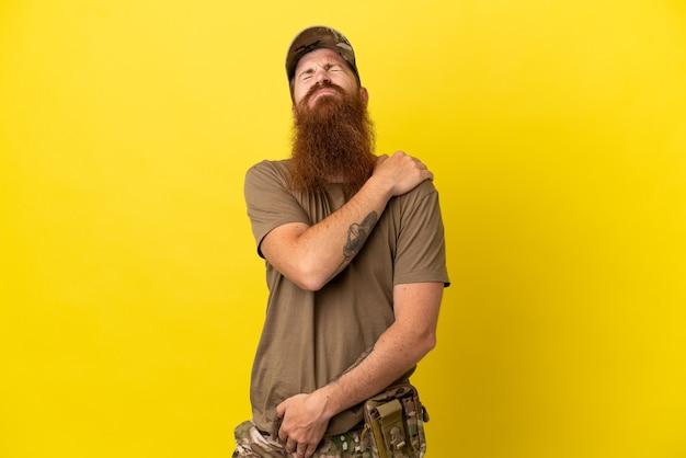 Militar ruivo com crachá isolado em fundo amarelo sofrendo de dores no ombro por ter feito esforço