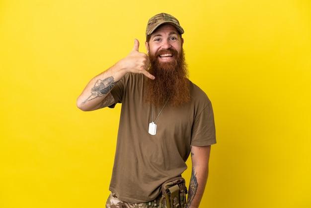 Militar ruivo com tag de cachorro isolada em fundo amarelo, fazendo gesto de telefone. ligue-me de volta sinal