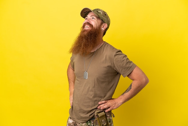 Militar ruivo com uma etiqueta de cachorro isolada em um fundo amarelo, posando com os braços na cintura e sorrindo