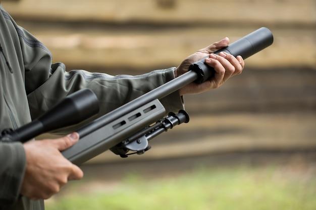 Militar segura uma pistola com silenciador