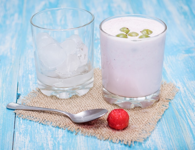 Milk-shake com morangos, groselhas e gelo em uma mesa azul.