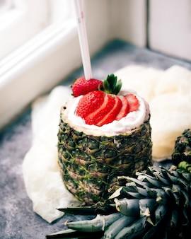 Milk-shake com morangos servidos dentro de abacaxi