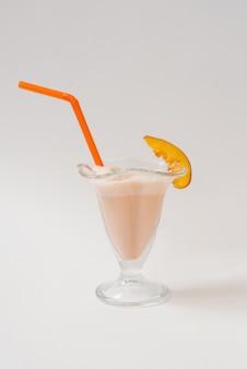 Milk shake com nectarinas em um copo com um tubo de plástico laranja nele sobre um fundo branco. o conceito de comida saudável e deliciosa