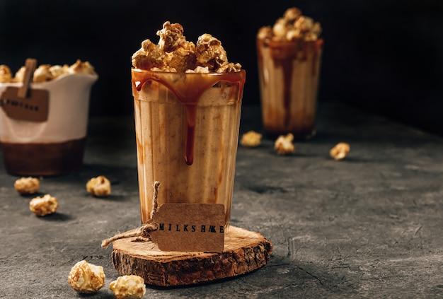 Milk-shake de banana com caramelo e pipoca em foco seletivo de fundo escuro