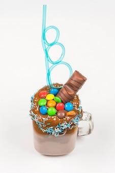 Milk-shake de chocolate com chantilly, biscoitos, waffles, servido em um frasco de vidro.