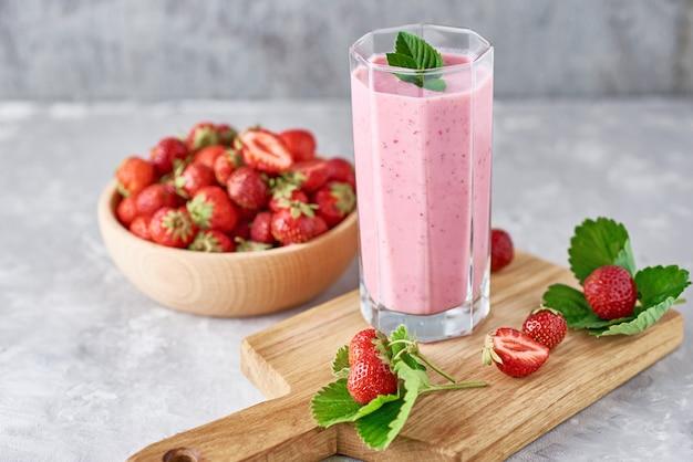 Milk shake de morango em uma jarra de vidro e morangos frescos com folhas