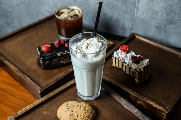 Milk-shake de vista lateral com chantilly e biscoitos em uma bandeja com bolos