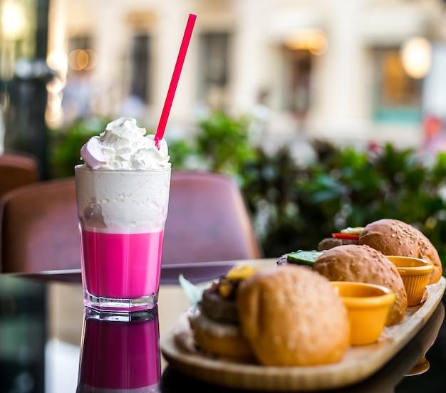 Milk-shake de vista lateral com chantilly e hambúrgueres