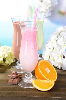 Milk shakes com frutas na mesa em fundo azul claro