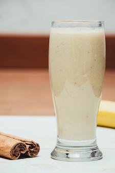Milkshake com banana, aveia e canela em copo, vista de cima, horizontal
