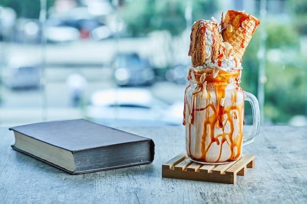 Milkshake de anel de caramelo na placa de madeira com livro.