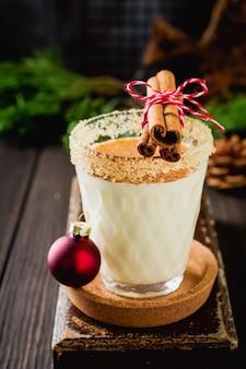 Milkshake de bebida de natal tradicional de gemada com canela em fundo escuro antigo. foco seletivo.