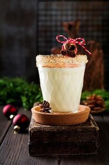 Milkshake de bebida de natal tradicional de gemada com canela em fundo escuro antigo.