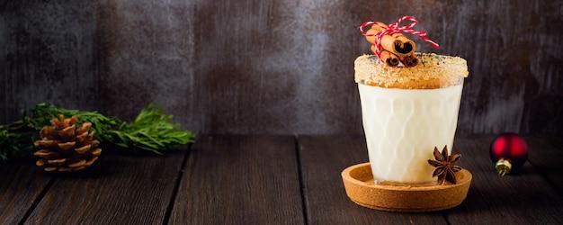 Milkshake de bebida tradicional de natal de gemada com canela em fundo escuro antigo