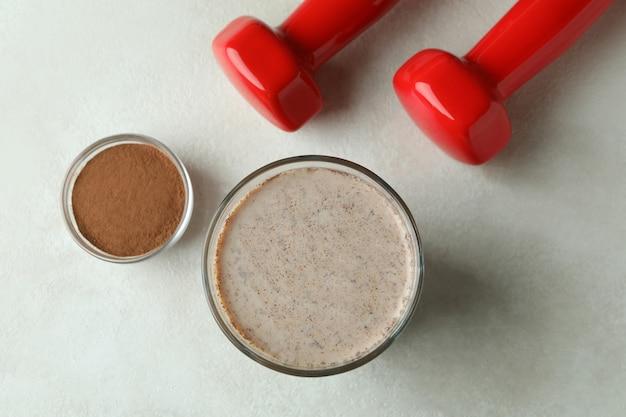 Milkshake de chocolate, chocolate em pó e halteres na mesa texturizada branca